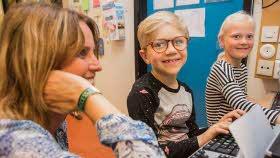 Två elever sitter framför en dator i ett klassrum tillsammans med en lärare. De är alla glada. Eleverna tittar in i kameran. De är båda ljushåriga. En har kort hår och glasögon, den andra har långt hår i en tofs. Läraren har ljusbrunt hår.
