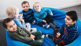 Fem nyfikna, små barn sitter tätt tillsammans i något som liknar en mjuk blå bassäng. Fyra av barnen har något blått på sig