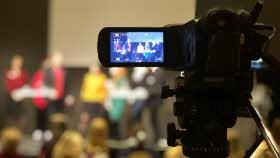 En filmkamera är riktad mot personer i en panel, kameran är i fokus, personerna är suddiga