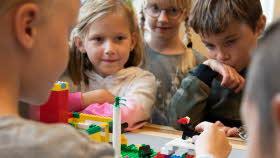 En grupp elever står runt ett bord med en miljö byggd i lego. En elev berättar om bockarna bruse med hjälp av miljön.
