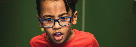 En pojke med glasögon tittar på något utanför bilden och ser lite bestört ut. Han rynkar lätt på ögonbrynen och munnen är öppen.