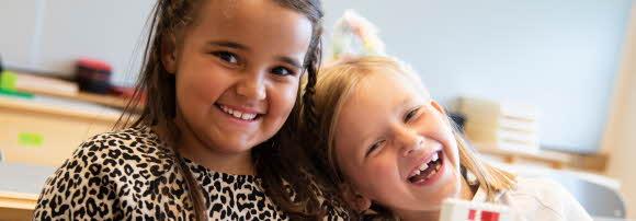 Två glada flickor tittar rakt in i kameran med huvudena tätt ihop.