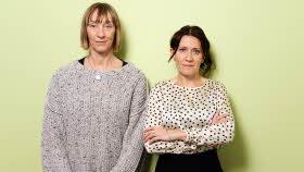 Två allvarliga kvinnor står framför en ljusgrön vägg. En har en prickig blus och står med armarna i kors. Den andra har en ljusgrå stickad tröja.