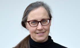 En kvinna med glasögon och långt, gråbrunt hår uppsatt i en tofs tittar rakt in i kameran och ler lite.
