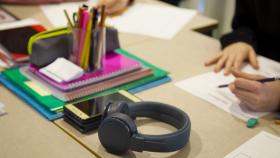 Ett bord fyllt med grejer, exempelvis ett par hörlurar, en mobiltelefon, anteckningsböcker.