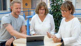 En man och två kvinnor sitter vid ett litet bord. På bordet finns en laptop. Mannen pekar på skärmen och kvinnorna tittar på skärmen. De sitter i skolmiljö.