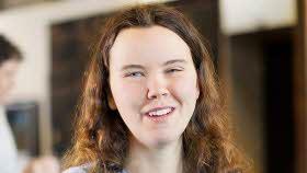 En ung kvinna ler och tittar in i kameran