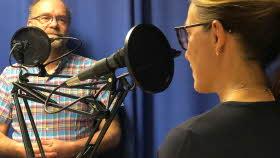 Två mikrofoner med puffskydd. Vid dem står en man och en kvinna. Mannen ser ut att lyssna på kvinnan, som syns snett bakifrån.
