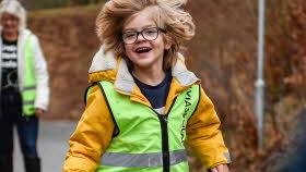 En pojke med glasögon springer utomhus så att håret flyger runt huvudet, han ler stort och tittar rakt in i kameran. Han har en gul jacka och en grön reflexväst på sig
