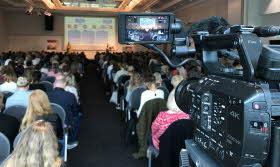 En fullsatt åhörarsal sedd från sista raden där det står en filmkamera riktad mot scenen.