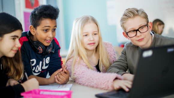 Elever samlade kring en dator.