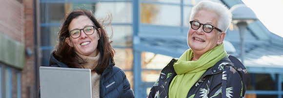 Två kvinnor står utanför en skola. Båda tittar in i kameran och ler stort.