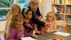 Fyra elever sitter vid ett bord, en lärare visar dem något och sträcker in sin arm över ett bord.