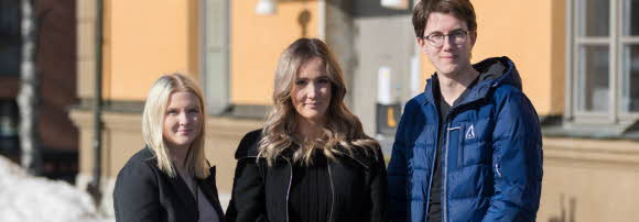 Två tjejer och en kille står framför sin gula gymnasieskola