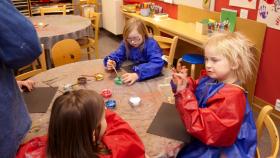 Några barn sitter och målar med pensel och färg
