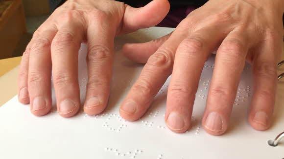 Händer som läser punktskrift