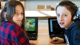 Två elever sitter vid sina datorer, de tittar in i kameran och ser allvarliga ut