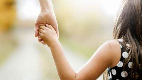 Bilden visar ett barn som håller en vuxen i handen