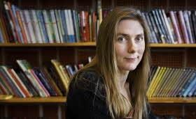 En kvinna med långt, brunt hår sitter på en bakåtvänd stol framför en bokhylla, hon tittar rakt in i kameran och ler lite.